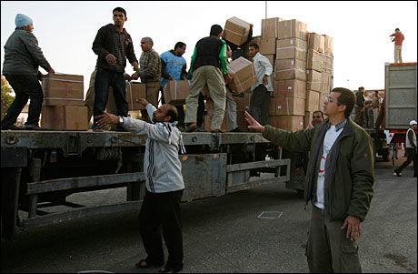 SLAPP IGJENNOM: Egyptiske hjelpearbeidere forberedte lastebiler med medisiner på grensen til Gaza mandag. Tirsdag slapp de igjennom. Foto: REUTERS
