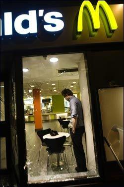 KNUSTE VINDUER: Dan Bjørke ved Mc Donalds i Grensen kikker ut gjennom de knuste vinduene i restauranten som ble knust av bråkmakere lørdag kveld Foto: SCANPIX