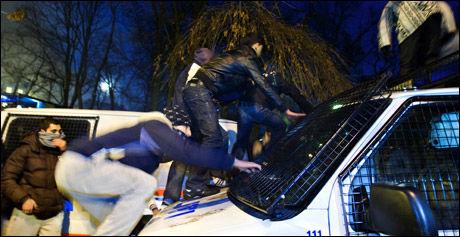 PÅ RØMMEN: Demonstrantene er omringet og prøver å rømme fra politiet ved å klatre over politibilene under en av demonstrasjonen foran Israels ambassade. Foto: FOTO: EIVIND GRIFFITH BRÆNDE