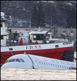 FLYTER: Flere båter klarte å hindre at flykroppen sank i Hudson-elva. Sent torsdag kveld ble havaristen fraktet inn til et kaiområde i Manhatten. Foto: Reuters