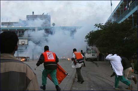 LØPER: Ambulansepersonell løper for å hjelpe skadde og slukke brannen etter at en FN-skole ble bombardert lørdag på Gazastripen. To barn skal være blant de drepte. Foto: AFP