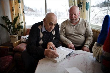 BOKSUKSESS: Boken om Snåsamannen har vært en kjempesuksess. Her signerer Joralf Gjerstad et eksemplar av boken hjemme i sin egen stue på Snåsa. Foto: THOR NIELSEN