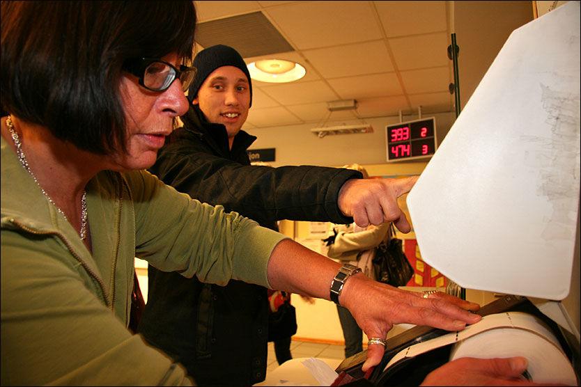 NY KØLAPP: Bertha Johansen må nok en gang skifte rull i kølappmaskinen til Nav i Akersgata. Denne gang får hun hjelp av Kim Billet, som skal purre på sykepengene. Foto: Gjermund Glesnes