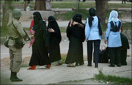 POLITI-HIJAB: Kvinnelige religiøse studenter overgir seg til paramilitære styrker 4. juli 2007. To politikvinner i hijab til høyre i lyseblå jakker. Foto: AP