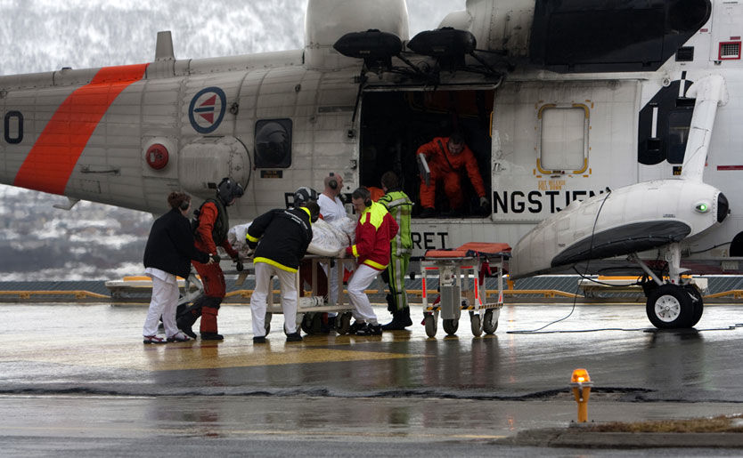 TIL SYKEHUS: En av mannskapet på den havarerte russiske tråleren Koralnes tas ut av et Sea King helikopter fra 330 skvadronen ved Universitetssykehuset i Nord-Norge i Tromsø fredag formiddag. Dette er en av de to som ble plukket opp av sjøen. Foto: Scanpix