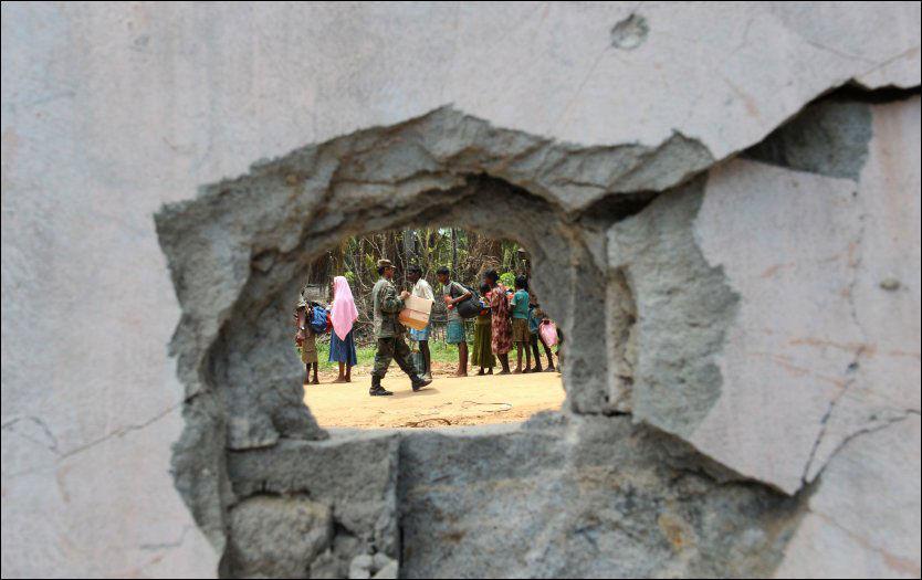 KULEHULL: En srilankisk soldat deler ut mat til tamilske flyktninger i Puthumathalan . Den srilankiske hæren hevder nå at de er på nippet til å knuse de tamilske opprørerne. Foto: AFP