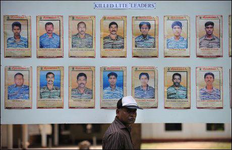 DREPTE TIGER-LEDERE: En journalist går forbi en veggplakat med bilder av LTTE-ledere drept av den srilankiske hæren uinder et pressebesøk til krigsområdene. Foto: AFP
