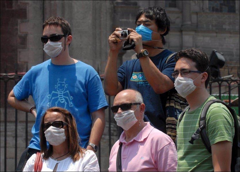 MUNNBIND: En gruppe turister bruker munnbind mens de tar bilder i Mexico City. Nå mener EU at Europa snart kan vente seg de første dødsfallene av svineinfluensaen. Foto: EPA