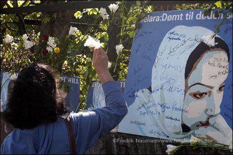 AKSJONERTE: En kvinne henger opp en hvit blomst i gjerdet utenfor den iranske ambassaden under en markering til støtte for Delara Darabi. Foto: Amnesty