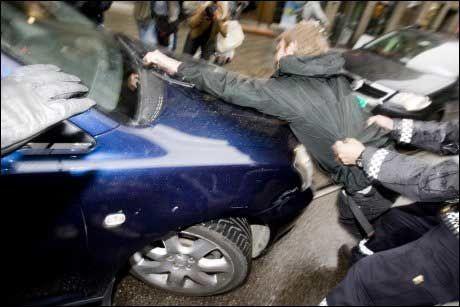 PRØVDE Å STOPPE HAM: David Irving ble på nytt møtt av demonstranter da han forlot TV2s studio i Oslo tirsdag ettermiddag. Politiet forsøkte å sperre gaten for både demonstranter, fotografer og biler for å få Irving ut fra området. Foto: Scanpix