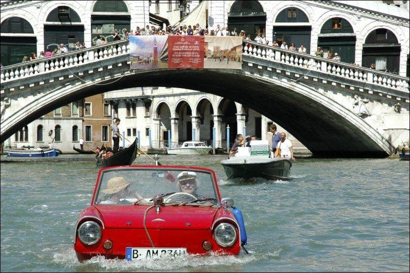 Bernd Weise kjører under Rialto-brua i Venezia. I bakgrunnen følger en gruppe turister med på den stilige amfibiebilen. Foto: REUTERS / Michele Crosera / SCANPIX