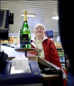 LOTTO-MILLIONÆR: Kjellfrid Elgåen fortsetter å spille, selv om hun allerede er lottomillionær. Her leverer hun inn en ny kupong i Joker-butikken på Drevsjø i Engerdal. Flasken med sprudlevann står og venter på bygdas neste storvinner. Foto: Annemor Larsen