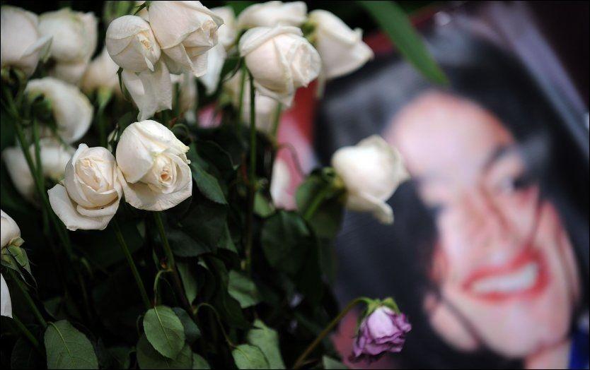 SØRGER: Fans over hele verden sørger. Blomster og bilder er lagt ned utenfor huset til Michael Jackson i Los Angeles. (Foto: AFP)