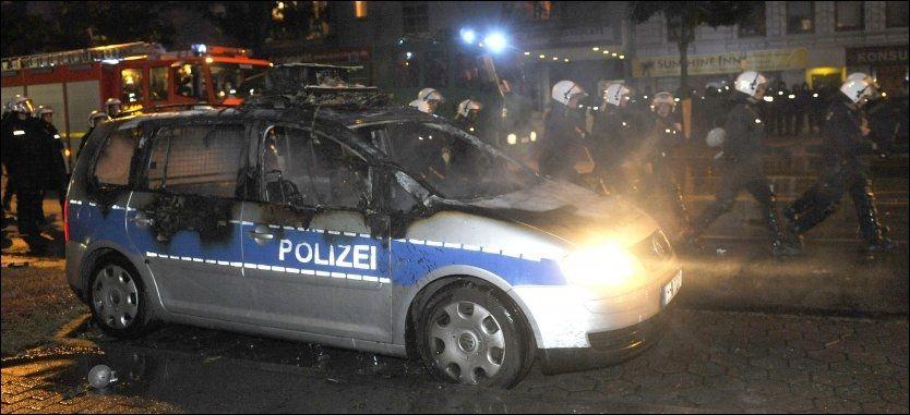 UTBRENT: Politiet passerer en utbrent politibil i Hamburg. 27 politimenn har blitt såret i opptøyene i den tyske byen. Foto: AP
