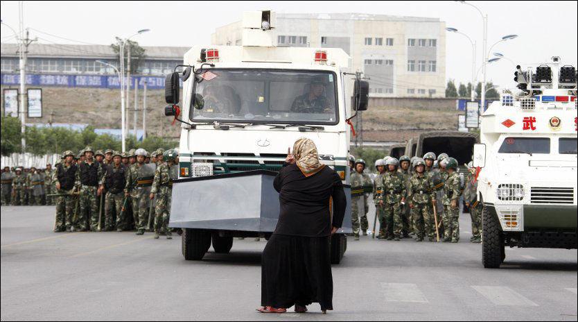 ALENE MOT POLITIET: Her hytter Tursun Ugul (30) med neven mot politiet og panserkjøretøyene. Foto: EPA