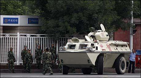 SPENT: Soldater og et pansret personellkjøretøy er utplassert like ved Folkets plass i Urumqi i dag. Foto: EPA