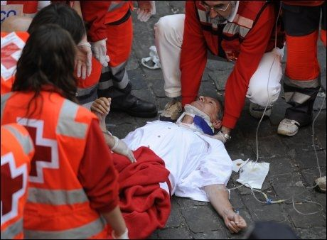SKADET: En franskmann kom seg ikke unna i tide, og trengte medisinsk hjelp under dagens okseløp. Foto: AFP