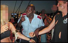 MÅ KYSSE: En «politimann» setter håndjern på en deltager på partycruiset og lenker henne fast til en ansatt. De må kysse for at han skal låse dem opp igjen. Foto: Mads A. Andersen