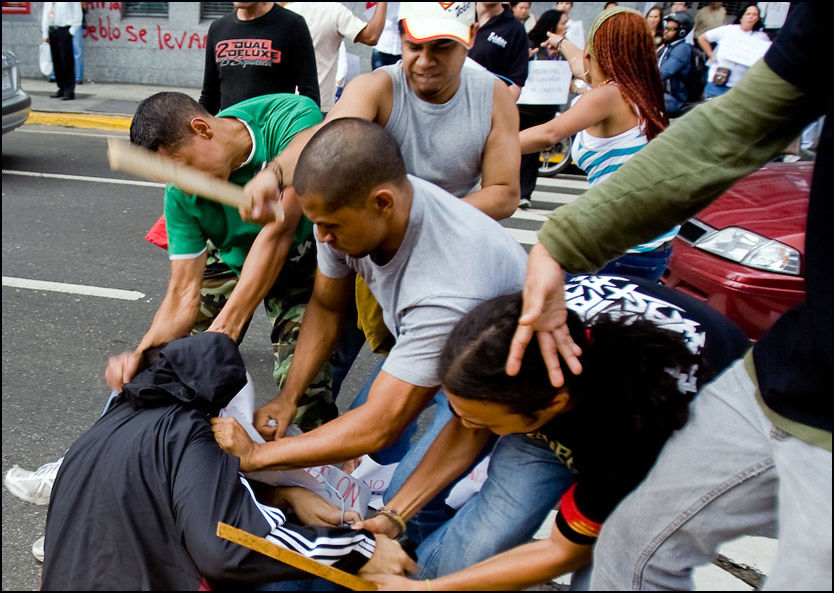 ANGREP MED PLANKER: Journalister som delte ut flygeblader mot den nye utdanningsloven som vil hindre fri presse, ble brutalt banket opp av noen av President Hugo Chávez fanatiske tilhengere. Foto: AFP Foto: