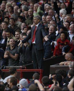 FIKK IKKE STÅ HER: Arsene Wenger fikk ikke lov å stå på tribunen bak benken. United-fansen rundt ham synes tydeligvis det var morsomt med celebert besøk. Foto: AP
