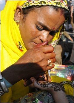 DEKORERER: En indisk kvinne dekorerer et barns hender med henna under feiringen av id al-fitr. Foto: AFP