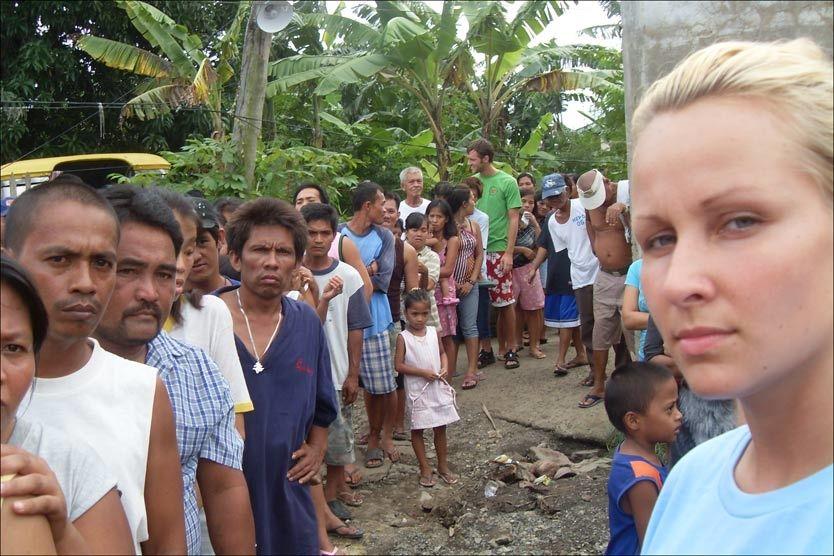 DELER UT MAT: Den norske legen Katharina Pracon (25) foran matkøene i Filippinene. Foto: Katharina Pracon