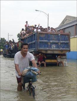 EVAKUERES: Flomrammede blir fraktet ut av Manila i store lastebiler. Foto: Katharina Pracon