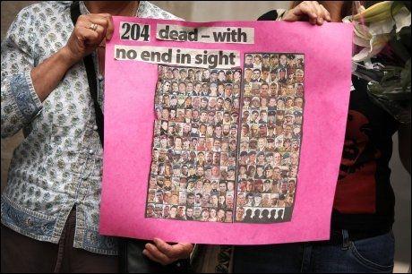MANGE DØDE: To kvinner holder opp bilder av de 204 døde soldatene som hadde blitt drept frem til august 2009 i Afghanistan. Nå er tallet opp i 219 døde, og krigen får stadig mer motstand i Storbritannia. Foto: AFP