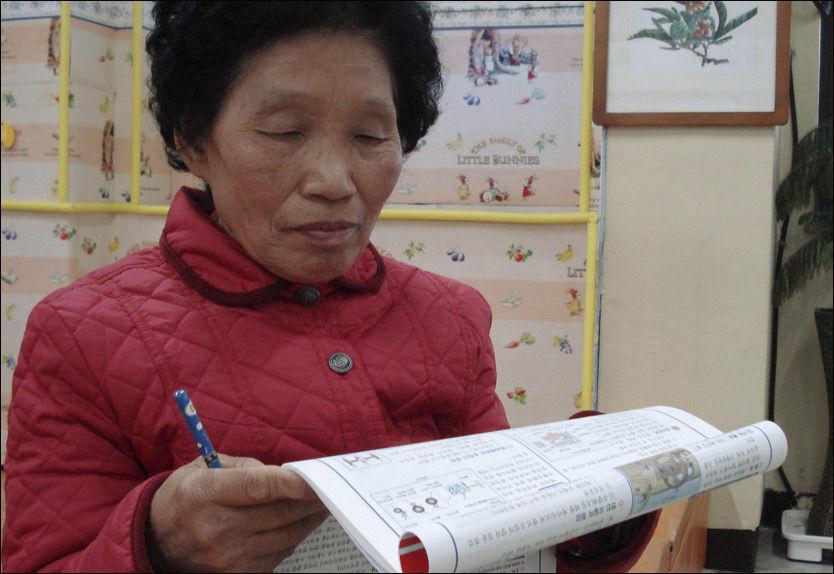 NOK ET FORSØK: Cha Sa-soon ser igjennom teorien før hun skal inn til test den 19. februar i år. Det var hennes 775 forsøk. Nå har hun endelig stått Foto: Reuters