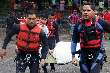 DØDELIG UVÆR: Redningsarbeidere bærer vekk et av ofrene for flommen i El Salvador. Foto: AFP