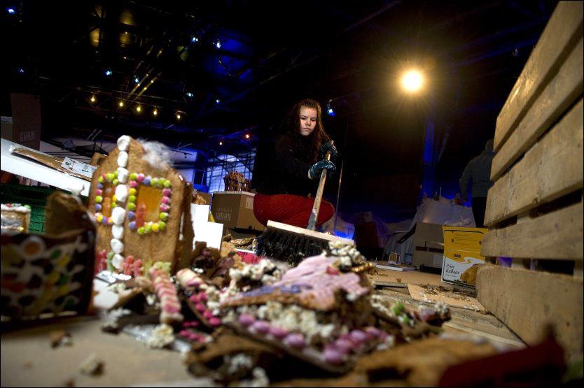 NON-STOP ØDELEGGELSE: Stine Veland (23) feier opp restene av pepperkakebyen. Hun har jobbet frivillig med pepperkakebyen hvert år siden hun var 12 år gammel. Foto: TOR ERIK H. MATHIESEN