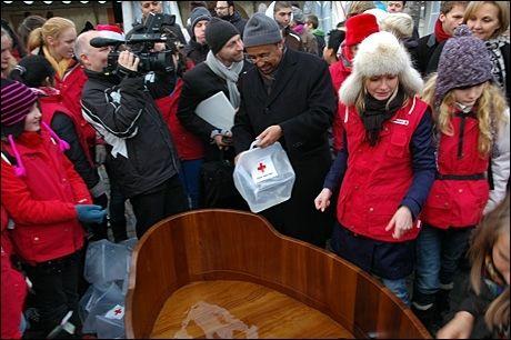 Generalsekretær Bekele Geleta i Den internasjonale Røde Kors og Røde Halvmåne-føderasjonen var med på å fylle kannene med vann. Foto: STIAN EISENTRÄGER