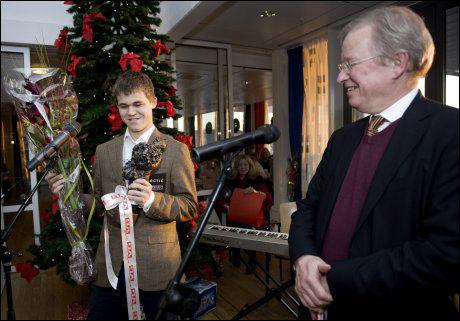 STOLT: Ansvarlig redaktør Bernt Olufsen delte ut statuetten som symboliserer at VG-leserne har kåret Magnus Carlsen til Årets navn. Premien på 50.000 kroner gir sjakk-kometen til UNICEF. Foto: Kristian Helgesen