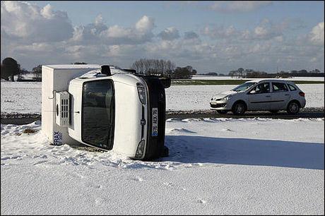 MYE SNØ: En bil har veltet i nærheten av den franske byen Le Havre. Snømengdene har ført til store trafikkproblemer i Frankrike. Foto: Reuters