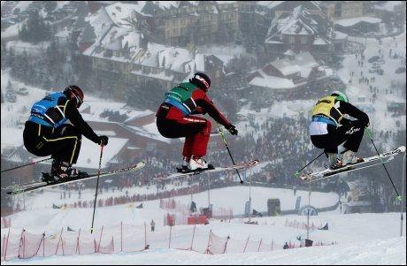 SPEKTAKULÆRT: Trippelhopp i skicrossrennet onsdag kveld norsk tid, dette bildet er fra herreklassen. Foto: AP