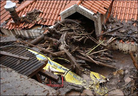 ØDELAGT: Deler av en taxi ligger mellom to hus etter å ha blitt ødelagt i uværet. Foto: REUTERS