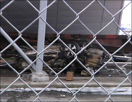 SMADRET: Her ligger en av bilene som ble smadret av det løpske godstoget. Vraket ligger under en av vognene og en smadret bygning på ulykkesstedet. Foto: