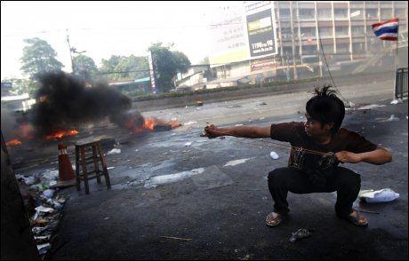 GATEKAMPER: Demonstrantene bruker spretterter, kastet steiner og setter fyr på bildekk i kampen mot soldatene som har omringet leiren deres i et område i sentrum av Bangkok Foto: Reuters/Scanpix