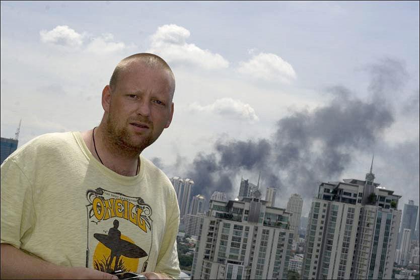 I BANGKOK: Lars Taraldsen (27) fra Risør bor med sin norske samboer i Bangkok. Røyken i bakgrunnen kommer fra de mange brannene i byen. Foto: Anniken Renslo Sandvik