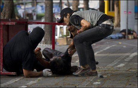 SKUTT: Minst 12 mennesker er drept i onsdagens kamper i Bangkok. Denne personen ble skadet etter å ha blitt skutt av en soldat. Foto: Reuters