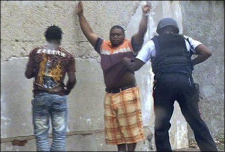 SPENT: En politimann ranssaker to personer i Kingston. Store politistyrker forsøker nå å få kontroll over uroen som preger Jamaicas hovedstad. Foto: