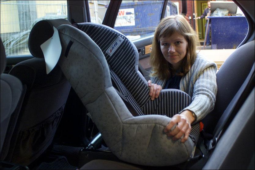 BAKOVERVENDT: Kommunikasjonssjef Kristin Øyen i Trygg Trafikk fester et bakovervendt barnesete i bilen. De fleste foreldre snur barnet i forovervendt posisjon altofr tidlig, ifølge trafikksikkerhetsorganisasjonen. Foto: Simen Storrud