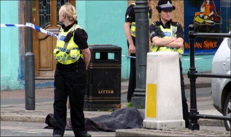 SKUTT I GATA: Polititjenestemenn står vakt på åstedet i Duke Street, i byen Whitehaven, hvor en person ble skutt tidligere i dag. Foto: Reuters Foto: