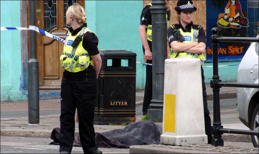 SKUTT I GATA: Polititjenestemenn står vakt på åstedet i Duke Street, i byen Whitehaven, hvor en person ble skutt tidligere i dag. Foto: Reuters