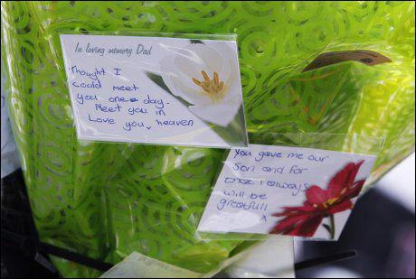 SISTE HILEN: Pårørende etter en drepte taxisjåføren Darren Rewcastle la ned blomster og hilsener på åstedet på taxiholdeplassen i Whitehaven. Foto: AP
