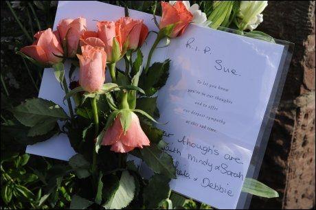 BLOMSTER: Et brev med en siste hilsen til Susan Hughes (57) er lagt ned med blomster i landsbyen Egremont. Foto: Reuters
