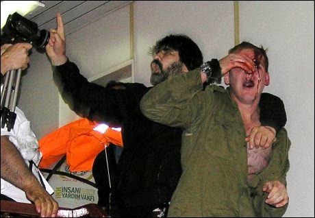 SKADET: En blødende og gråtende elitesoldat fra den israelske hæren er tatt til fange av aktivistene på «Mavi Marmara». Foto: AFP