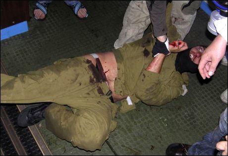 RIBBET FOR UTSTYR: Aktivistene tar en soldat til fange, og fjerner alt sikkerhetsutstyr. Til høyre i bildet ses en uidentifisert deltager med kniv i hånden. Foto: AFP