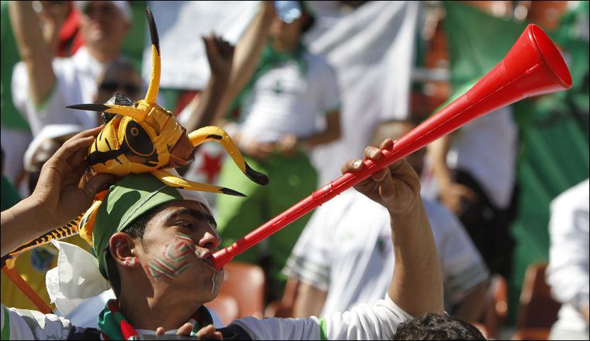 BLÅSER I KAMPEN: En algerisk fan blåser det han kan i den etter hvert så velkjente vuvuzelaen. Nå kan det være slutt. Foto: AP Photo.