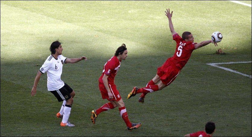 HER SKJER DET: Namanja Vidic kaster seg frem og handser inn i eget felt. Heldigvis for United-stopperen misset Podolski fra 11-meteren. Foto: Reuters